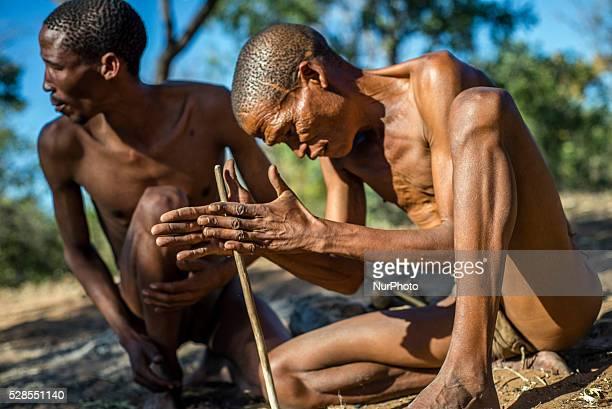 San men make fire in the Living Museum of the JuHoansiSan Grashoek Namibia