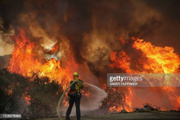 San Miguel County Firefighters battle a brush fire along Japatul Road during the Valley Fire in Jamul, California on September 6, 2020 - The Valley...