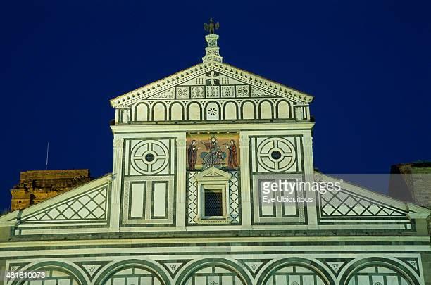San Miniato al Monte Romanesque church facade with geometric marble patterning illuminated at night