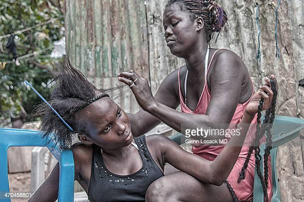 San Pedro de Macoris Dominican Republic slums, local beauty parlor. One woman with keloids on her arm combs out hair of another seated woman who...