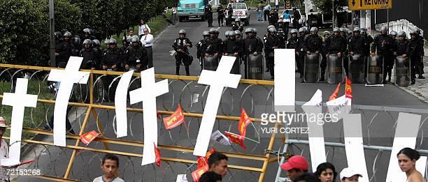 Un grupo de miembros del Movimiento de Resistencia Popular 12 de Octubre colocan cruces blancas en una alambrada frente a policias antimotines que...
