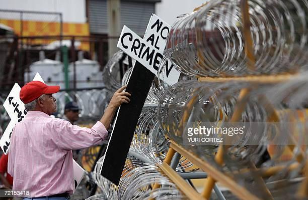 Un miembro del Movimiento de Resistencia Popular 12 de Octubre coloca una cruz en una alambrada colocada por policias antimotines que resguardan una...