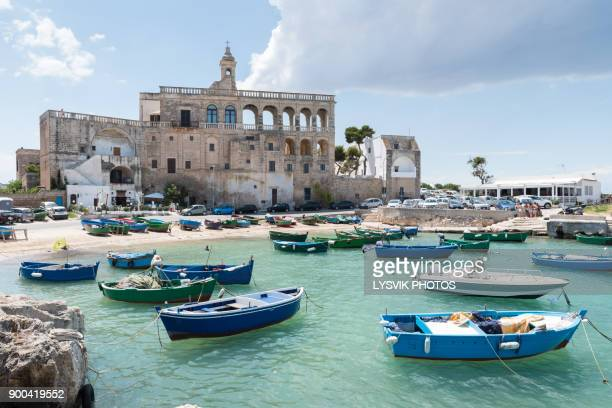 san vito port with old abbey and colorful fischerboats - polignano a mare stock photos and pictures