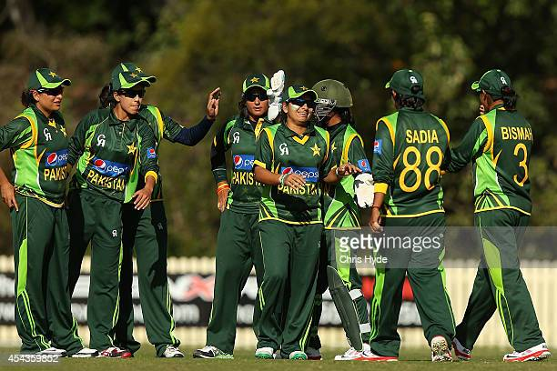 Sana Mir of Pakistan celebrates with team mates after dismissing Jess Jonassen of Australia during the women's international series T20 match between...