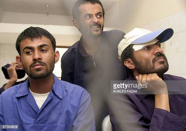 Three unidentified Yemeni suspects listen to the judge from behind court bars at the final hearing session of their trail in Sanaa 29 March 2006 Four...