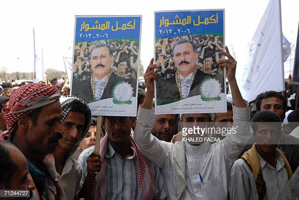 Yemeni people carry pictures of President Ali Abdullah Saleh during a rally held in Sanaa 20 June 2006 calling Saleh to run in the upcoming...