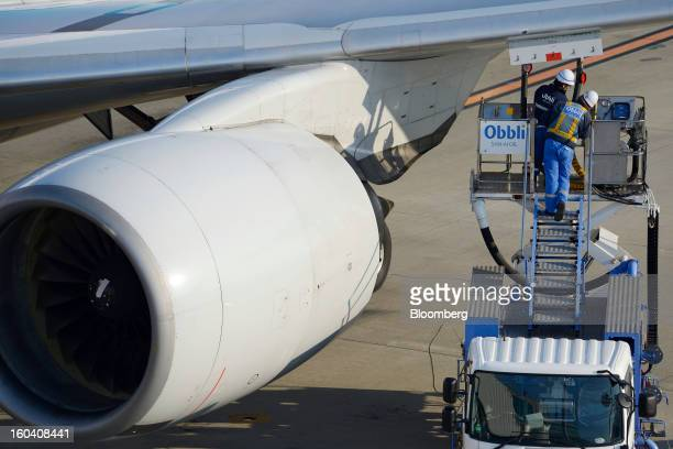 SanAi Oil Co employees stand on a fuel truck as they refuel an All Nippon Airways Co aircraft at Haneda Airport in Tokyo Japan on Wednesday Jan 30...