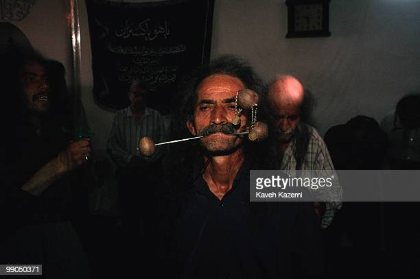 A dervish in trance during remembrance ceremony of Kasnazani sect which with three skewers pushed into his cheeks and his jaw In the background...