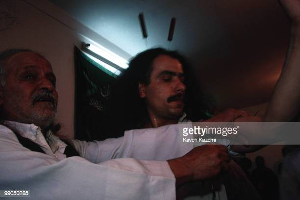 During remembrance ceremony a Kasnazani dervish while in trance has two knives in his skull and one skewer being put through his arms by the Shaikh...