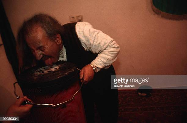 Khalife Hamma licks on a hot kerosene heater during a remembrance ceremony at his home in Sanandaj located in Kurdistan region of Iran Kasnazani...