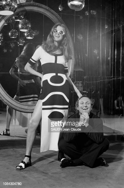 Séance photo avec Louis FERAUD souriant et assis par terre en tailleur posant avec un mannequin portant une tenue de sa collection printempsété 1971...