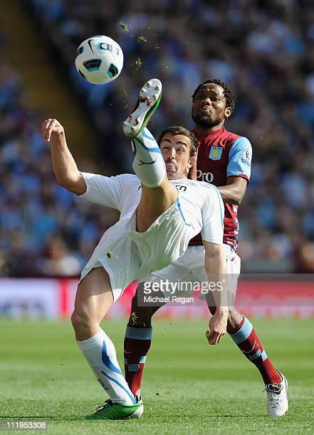 Sanchez Jose Enrique of Newcastle United kicks the ball under pressure from Jean Makoun of Aston Villa during the Barclays Premier League match...
