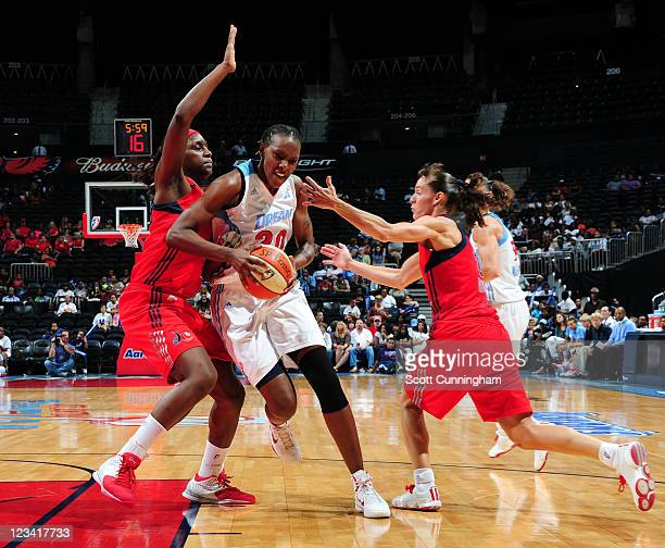 Sancho Lyttle of the Atlanta Dream drives against Crystal Langhorne and Kelly Miller of the Washington Mystics at Philips Arena on September 2 2011...