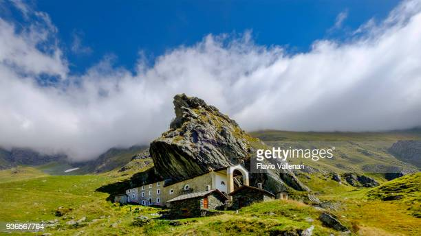 Sanctuary of San Besso, built with a side wall adjacent to the monolithic rock of Mount Fautenio. It is located in Valle Soana, a valley on the southern slope of the Gran Paradiso massif. Gran Paradiso National Park, Piedmont, Italy