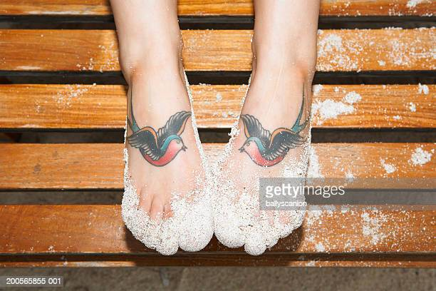 Sand and two tattooed swallows on woman's feet, close-up