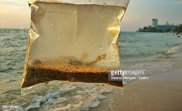 Sand And Water In Plastic Bag On Beach
