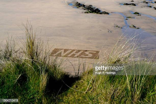 Sand artist Chris Howarth creates an NHN logo as part of his beach artwork at Gwithian on February 26, 2021 in Hayle, England. The NHS are expecting...