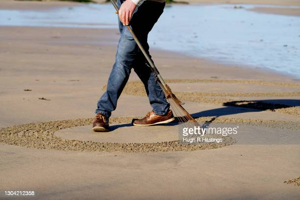 Sand artist Chris Howarth creates his beach artwork at Gwithian on February 26, 2021 in Hayle, England. The NHS are expecting a busy summer in...