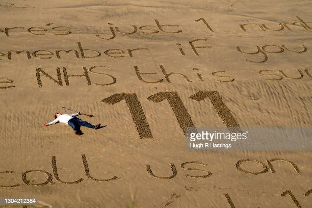 Sand artist Chris Howarth rests after creating his beach artwork at Gwithian on February 26, 2021 in Hayle, England. The NHS are expecting a busy...