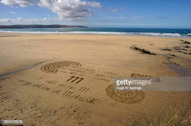 """Sand artist Chris Howarth""""u2019s finished artwork at Gwithian on February 26, 2021 in Hayle, England. The NHS are expecting a busy summer in Cornwall..."""