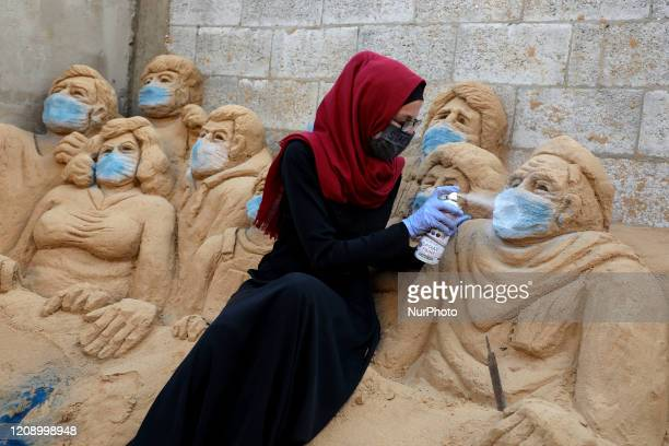 Sand Artist Rana Ramlawi works on her sand sculptures depicting the earth with a message reading quotStay Homequot at her home in Gaza City during...