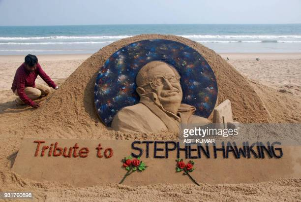 TOPSHOT Sand artist Sudarsan Patnaik gives final touches to a sculpture in honour of British physicist and awardwinning author Stephen Hawking at...