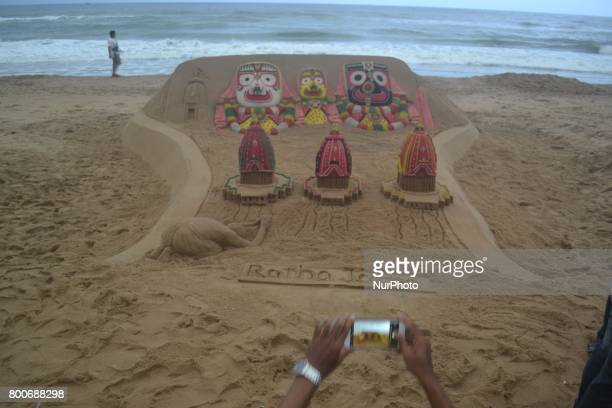 Sand artist Sudarshan Patnaik gives finishing touches to his chariot sand sclupture on the occassion of ditties annual rath yatra festival or chariot...
