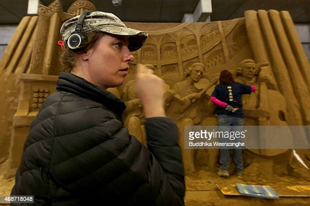 Sand artist Susanne Ruseler of Holland looks on her sand sculpture during the work ahead of 'Germany and Once Upon a Time' exhibition at the Sand...