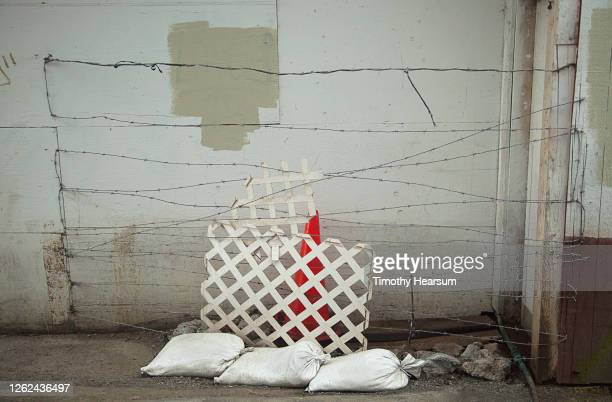 sand bags, pieces of lattice fence, barbed wire and a traffic cone against an old building in an alley - timothy hearsum photos et images de collection