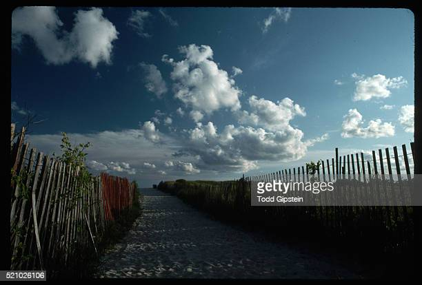 sand beach path with clouds overhead - gipstein stock pictures, royalty-free photos & images