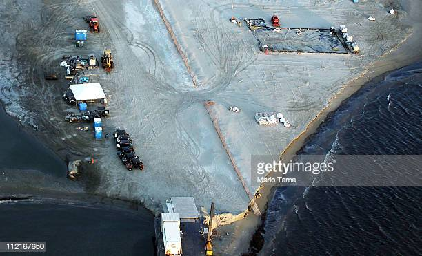 A sand berm built to capture oil from the BP spill is seen at an oil cleanup site in Barataria Bay April 13 2011 in Barataria Bay Louisiana Barataria...
