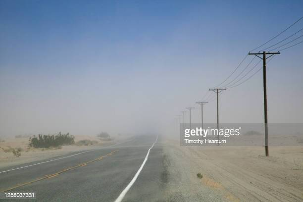 sand blows across a paved road with power poles lining one side; dust and blue sky beyond - timothy hearsum imagens e fotografias de stock