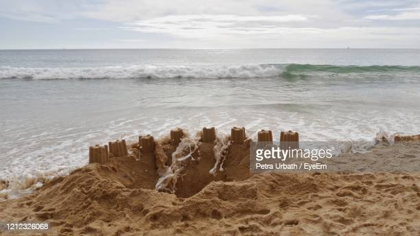 sand castle catched by waves - tide stock pictures, royalty-free photos & images