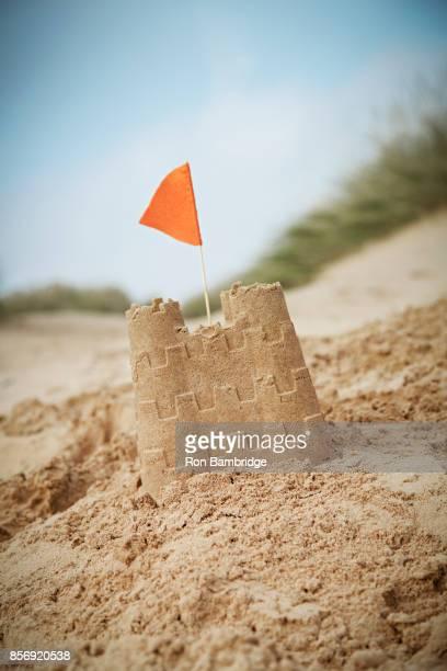 sand castle on UK beach with orange flag