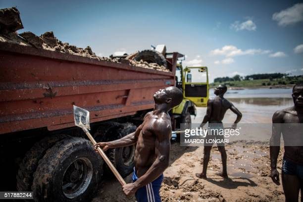 TOPSHOT Sand diggers are seen loading trucks at a quarry on the banks of the Congo river in the Kombe district of Brazzaville on March 28 2016 LONGARI