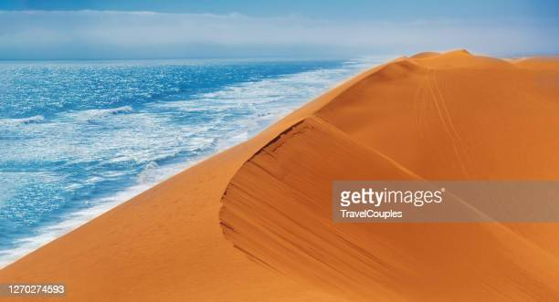 sand dunes and ocean near walvis bay, namibia. coast of the atlantica ocean at the namib-naukluft national park, namibia, south of africa. - ナミブ砂漠 ストックフォトと画像