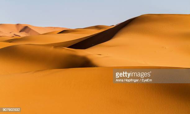 sand dunes in desert against clear sky - merzouga stock pictures, royalty-free photos & images