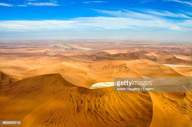 Sand Dunes In Desert Against Cloudy Sky
