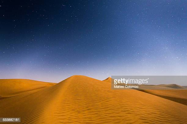 Sand dunes in the desert under a starry sky, Oman