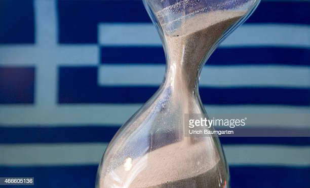 Sand glass and a Greek flagOur picture shows a running sand glass and the Greek flag