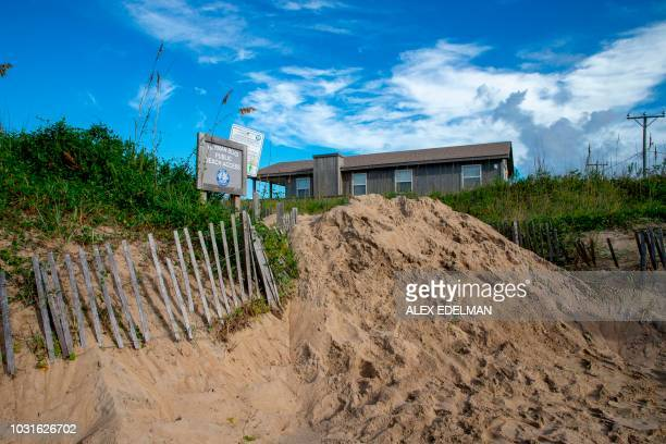 Sand is piled up to block a public beach to prevent storm surges in Kill Devil Hills on the Outer Banks of North Carolina September 11 as residents...