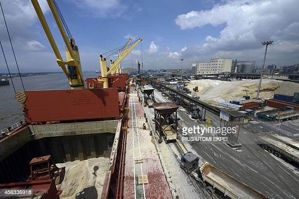 Sand is unloaded from the vast hold of the MV Pintail cargo ship into waiting trucks at the port of Apapa in Nigeria's financial capital in Lagos on...