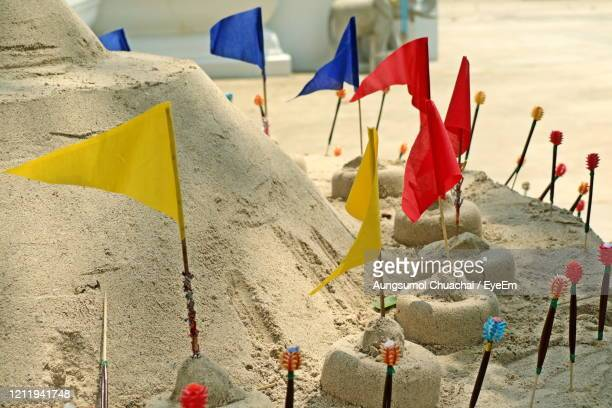 sand pagoda of songkran festival, thailand, with colorful paper flags on the pile of sand. - aungsumol stock pictures, royalty-free photos & images