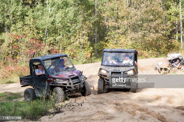 sand pit riding on 4x4 side-by-side off-road vehicles - side by side stock pictures, royalty-free photos & images
