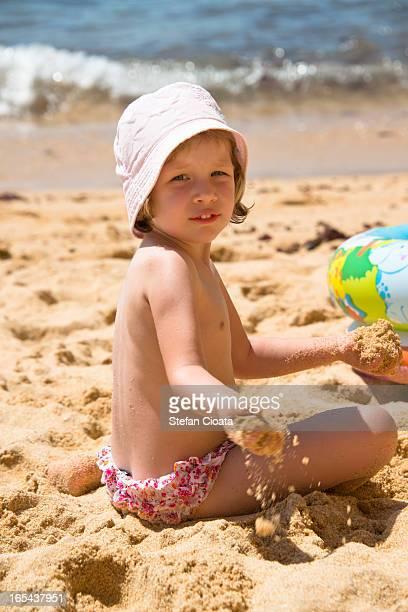 sand play and ocean bokeh - petite fille culotte photos et images de collection