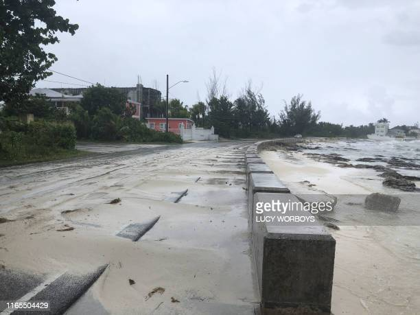 Sand pours on to a road near the beach during the approach of Hurricane Dorian on September 1, 2019 in Nassau, Bahamas. - Hurricane Dorian...
