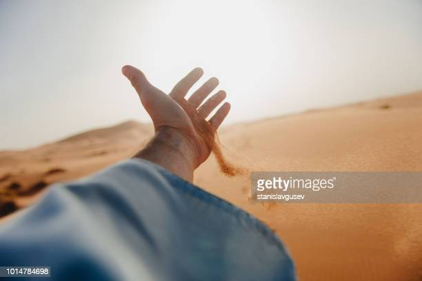 sand running through a man's hand in the desert, morocco - subjektive kamera ungewöhnliche ansicht stock-fotos und bilder