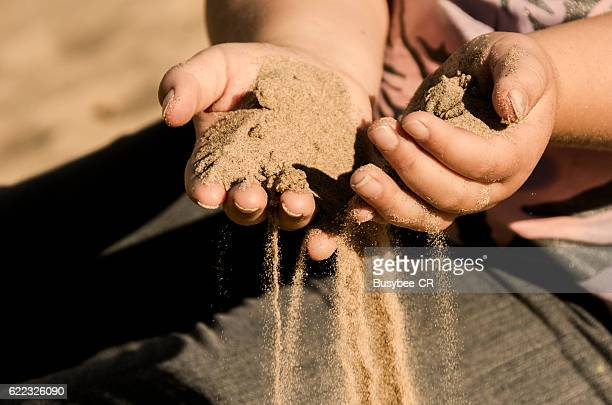 Sand running through fingers
