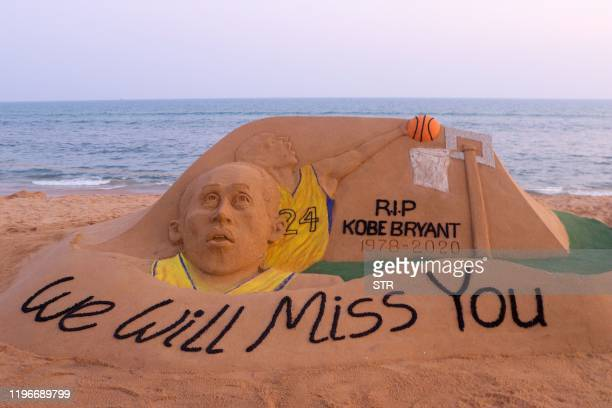 TOPSHOT A sand sculpture by Indian artist Sudarsan Pattnaik depicting American professional basketball player Kobe Bryant with the message 'we will...
