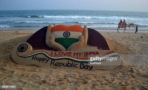 A sand sculpture is seen creating by Indian sand artist Sudarshan Pattnaik on the eve of Republic Day celebration at Puri on the eastern cost of Bay...